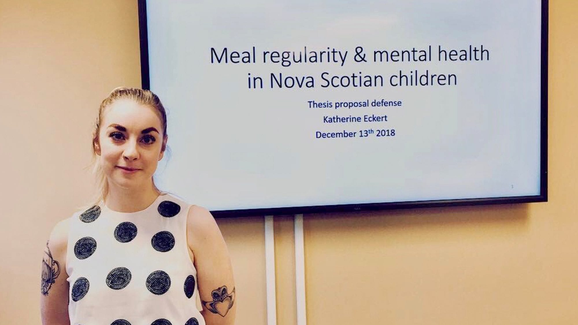"""Katherine poses in front of screen showing the title of her presentation, """"Meal regularity and mental health in Nova Scotian children"""""""