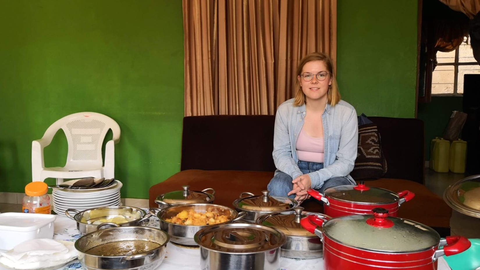 Regan poses behind a table covered in pots of food.