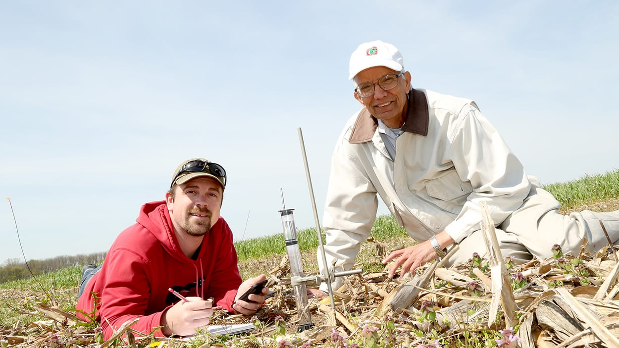 Dr. Lal and a researchers sit on the ground examining soil with scientific instruments.