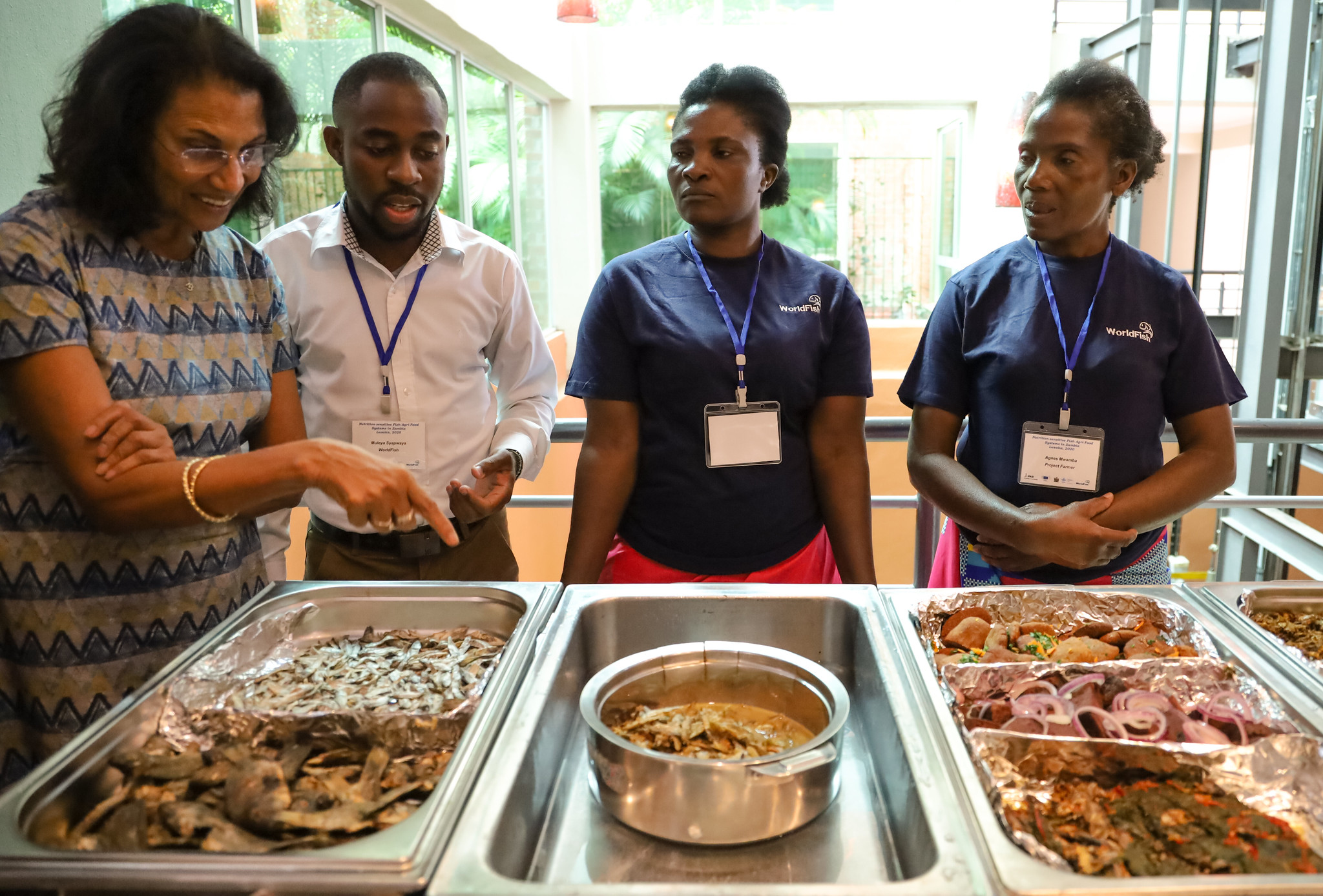 Dr. Thilsted and conference attendees looks at some small fish served in hot plates